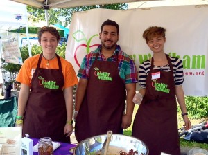 Interns Abbie. Manny and Yuki at the Healthy Waltham table at the Farmers Market, Summer 2014